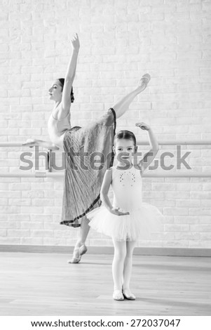 Young ballerina and her little daughter on training in dance class - stock photo