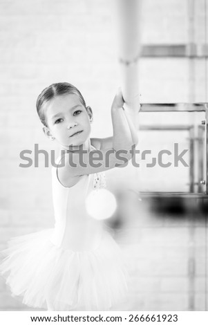 Young ballerina in white clothes is standing at a ballet class. - stock photo