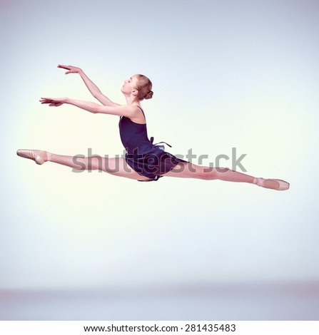 young ballet dancer jumping on a grey background. Ballerina is wearing in blue dress and pointe shoes - stock photo