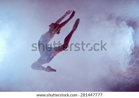 young ballet dancer jumping on a lilac background. Ballerina is wearing in blue dress and pointe shoes. The outline shooting - silhouette of girl with smoke effect - stock photo