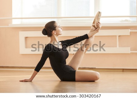Young ballet dancer performing exercise while sitting on floor - stock photo