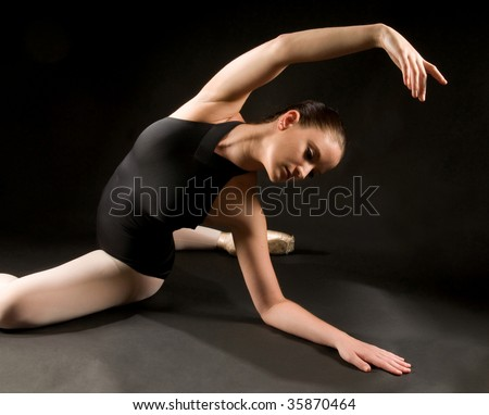 Young ballet dancer posing and stretching on the floor - stock photo