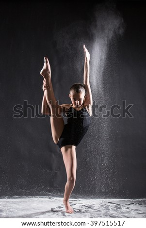 Young ballet dancer with flying powder doing the splits - stock photo