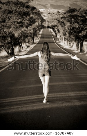 Young barefeet woman balancing in the middle of the road - stock photo