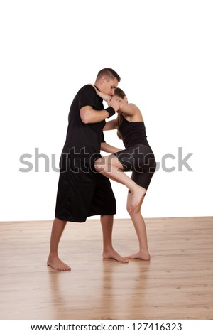 Young barefoot female kick boxer in training with her male instructor learning the moves as he demonstrates the technique - stock photo