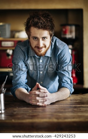 Young barman leaning on wooden bar counter and smiling at camera - stock photo