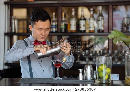 Young barman pouring cocktail into martini glass - stock photo