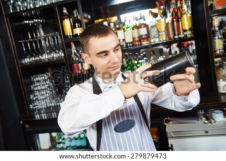 young barman worker at bartender desk in restaurant bar preparing coctail with shaker - stock photo
