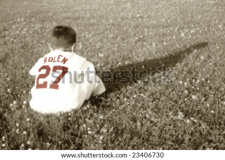 Young Baseball Boy Sitting in Grass - stock photo