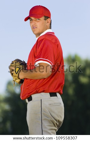 Young baseball pitcher holding mitt - stock photo