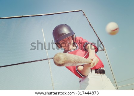 Young baseball player hitting the ball.  Vintage instagram effect - stock photo