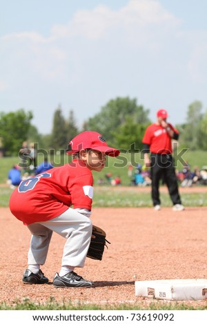 Young baseball player watching over third base - stock photo