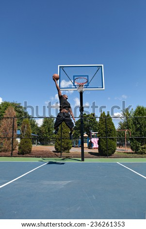 Young basketball player flying to the hoop for a monster jam. - stock photo