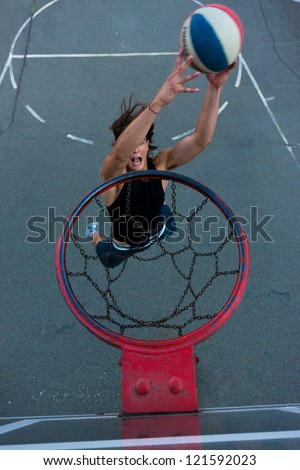 Young basketball player on the street going to the hoop. Great angle from above. Focused on the basket - stock photo
