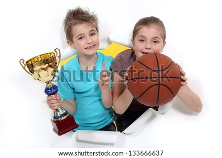 Young basketball players holding a trophy - stock photo