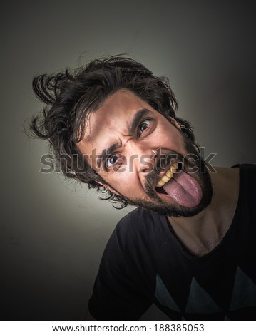 Young bearded and disheveled sticking out her tongue - stock photo