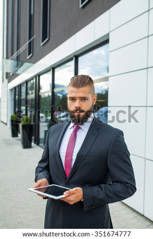 Young bearded businessman writting business e-mail using his tablet pc. Outdoor photo - stock photo