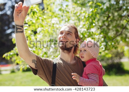 Young bearded hipster father with his cute little daughter taking selfie outdoors - stock photo