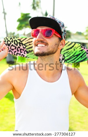 Young bearded hipster man in summer sunglasses reflecting palm trees,and cap,posing on the beach with skateboard.Travel Lifestyle concept on palm beach  background.California style,summer portrait - stock photo