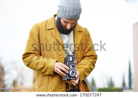 Young bearded hipster taking photo with TLR camera outdoors - stock photo