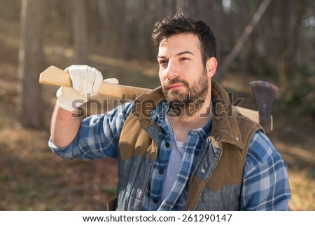 Young bearded lumberjack guy carrying an axe on his shoulder - stock photo