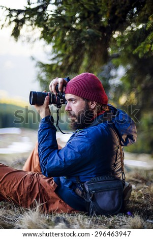 young bearded male with camera in the wood, photographer taking photos in mountains - stock photo