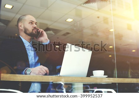 Young bearded man CEO of big successful company is having mobile phone conversation with customers, while is sitting with portable laptop computer in modern restaurant interior during work break - stock photo