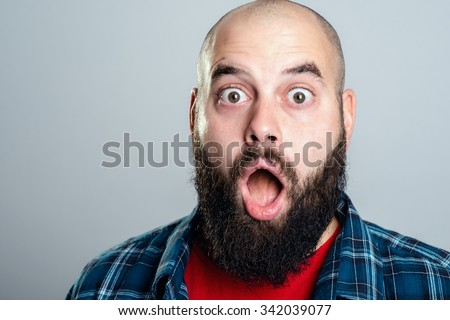 young bearded man looking amazed in to the camera - stock photo