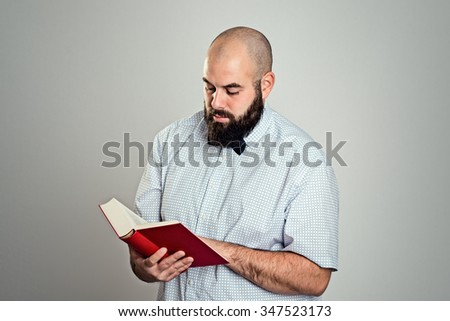 young bearded man reading a book in front of gray background - stock photo
