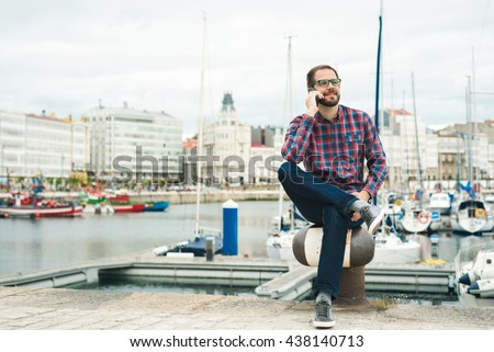 Young bearded man talking on cellphone outdoors at an urban harbour. - stock photo