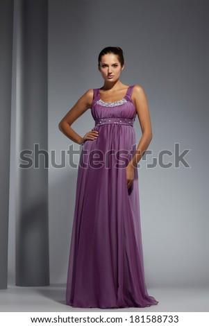 Young beautiful adult girl wearing elegant evening dress. Studio shot - stock photo