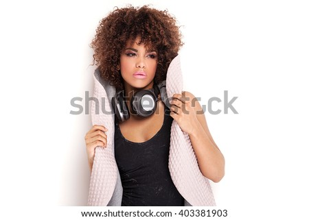 Young beautiful african american girl with headphones, listening to music. Studio shot. Portrait. - stock photo