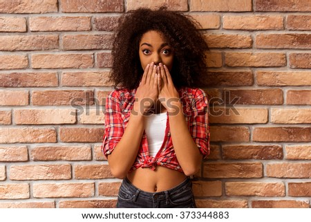 Young beautiful Afro-American woman posing and covered her mouth while standing against brick wall - stock photo