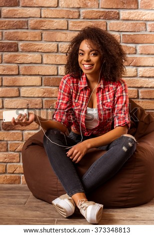 Young beautiful Afro-American woman using mobile phone, listening to music, looking in camera and smiling while sitting cross-legged on beanbag chair against brick wall - stock photo