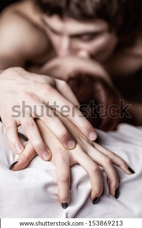 Young beautiful amorous couple making love in bed. Focus on hands - stock photo