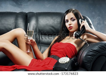 Young, beautiful and glamour woman in red dress with the vintage telephone on the leather sofa - stock photo