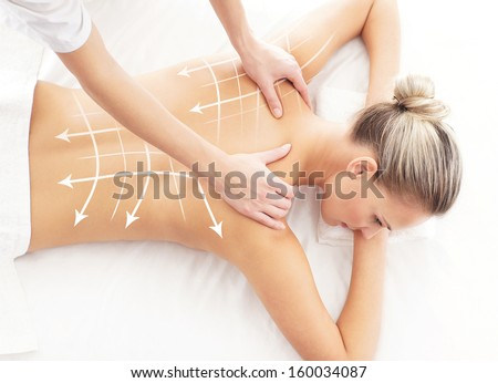 Young, beautiful and healthy woman getting alternative massage treatment (composition with the arrows) - stock photo