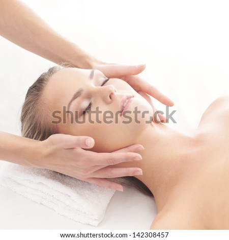 Young, beautiful and healthy woman getting spa treatment isolated over white background - stock photo
