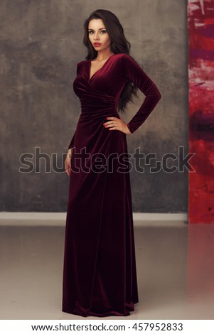 Young beautiful and pretty elegant woman in long cherry red evening dress posing against gray concrete wall. Portrait of smiling happy cheerful girl - stock photo