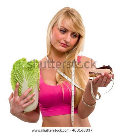 Young beautiful and sad girl with tape measure holds a cabbage on her right hand and looks at a piece of cake on her left hand, isolated over white background - stock photo