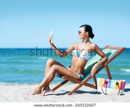 Young, beautiful and sexy woman with a sun protection cream on a summer beach - stock photo