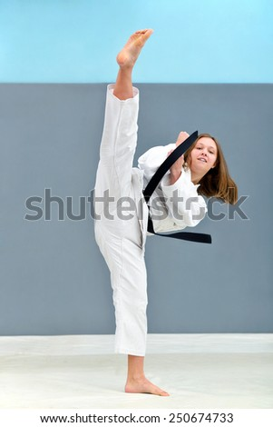 young, beautiful and successful woman karate, kick attack - stock photo