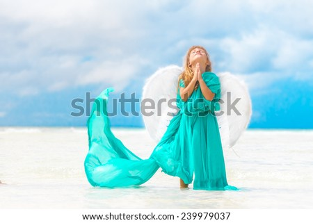 young beautiful angel child girl on natural sea and sky background - stock photo