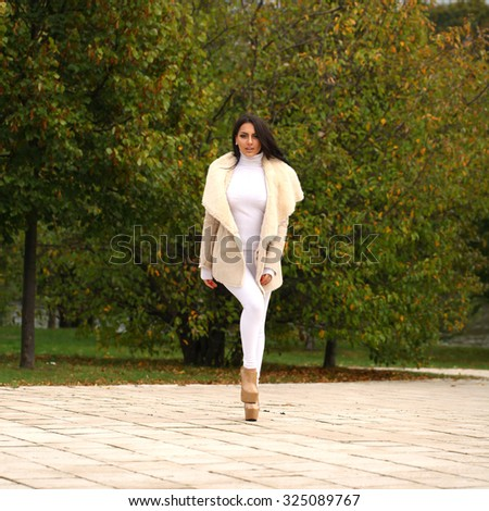 Young beautiful arabic brunette women in white sheepskin coat walking in autumn park - stock photo