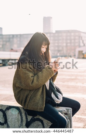 young beautiful asian hipster woman in the city back light using smart phone hand hold, tapping and scrolling the screen - technology, communication, social network concept - stock photo