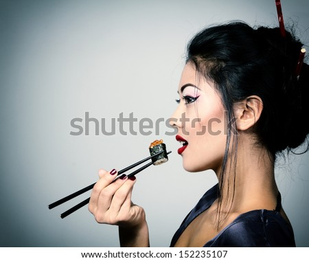 Young beautiful asian woman eating sushi with chopsticks, toned image and noise added - stock photo
