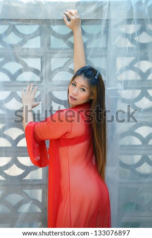 Young beautiful Asian woman naked outdoor. Wearing red transparent robe and bra no underpants, standing against wall. - stock photo