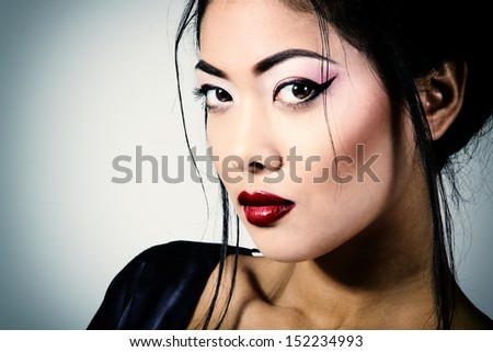 Young beautiful asian woman's portrait, studio shot toned and noise added - stock photo