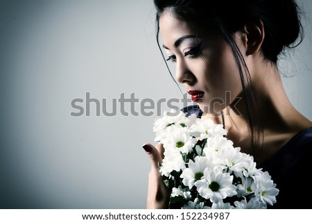 Young beautiful asian woman's portrait with white flowers, studio shot toned - stock photo