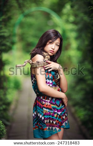 Young, beautiful asian woman with snake outdoor - stock photo